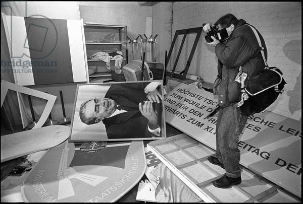 Photographer inside the building during an evening demonstration about the closing of the Ministery for State Security in East Germany, 15th January 1990 (b/w photo)