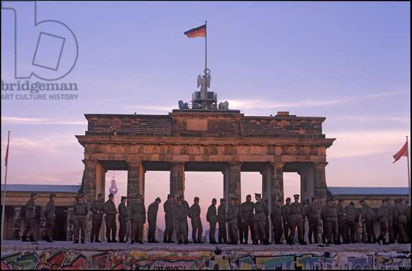 DDR border officials preventing Berliners from East and West climbing on the Berlin Wall by the Brandenburg Gate, 11th November 1989 (photo)
