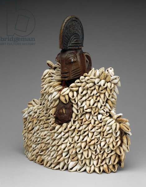 Twin Figure (ere ibeji) with Garment, 1940-1960 (wood, cowry shells, cotton cloth, sacrificial matter, plastic beads, nails, and traces of indigo)