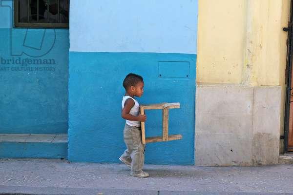 Boy carrying stool, Havana, Cuba (photo)