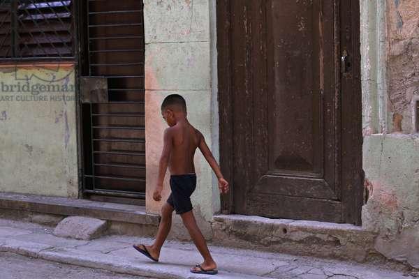 Boy walking, Havana, Cuba (photo)