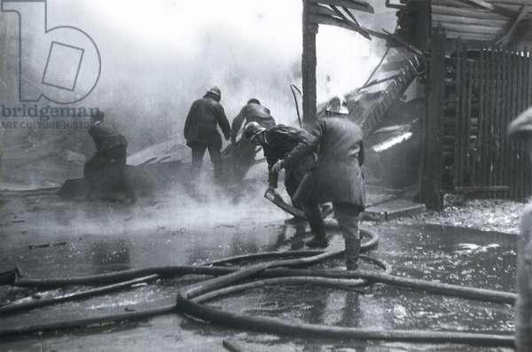 """Guerre civile espagnole (1936-1939) : pompiers et membres de la """"""""Defensa Pasiva"""""""" apres un bombardement dans le quartier de la Barceloneta. Barcelone, avril 1938."""