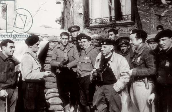 Spanish Civil War (1936-1939): defense of Madrid. Antonio Ortega speaking to other commanders has a barricade, Madrid, 1936 (photo)