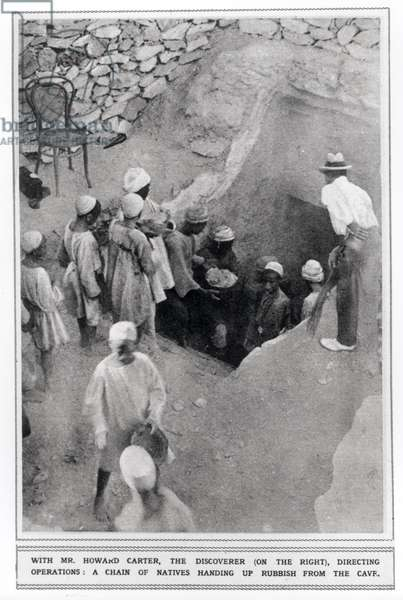 Howard Carter (1874-1939) directing operations as a chain of natives hand up rubbish from the cave (b/w photo)