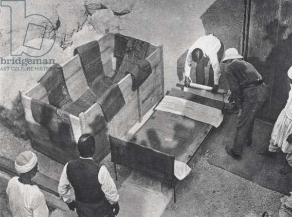 One of the royal beds being lifted into a box for removal from the Tomb of Tutankhamun (b/w photo)