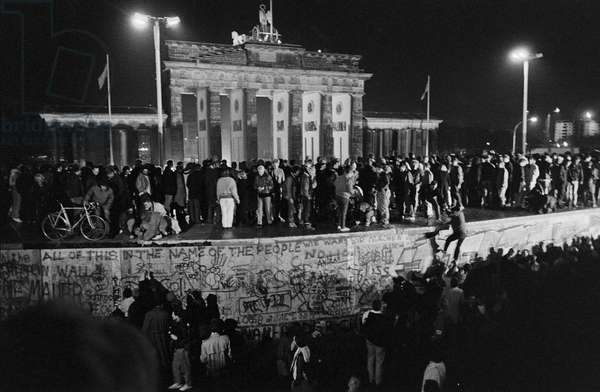 Fall of the Berlin Wall in November 1989: East and West Berlin climbed on the wall at the Brandenburg Gate on the night of 9-10 November 1989. Berlin, Germany. Fall of the Berlin Wall, people from East and West Berlin climbing on the Wall at the Brandenburg Gate, Berlin, Germany, Europe Photo Norbert Michalke