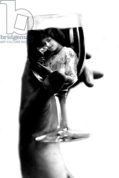 Hand holding a glass of wine in which a young woman is reflected with a glass of champagne. Photography around 1910
