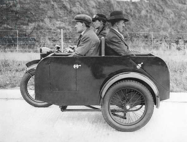 Three men driving a three-wheeled car.