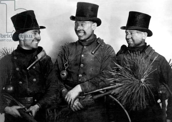 Portrait of three chimney sweaters covered in soot. Photography around 1920