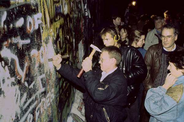Fall of the Berlin Wall in November 1989: Berlin broke the wall in the night of 9-10 November 1989. Berlin, Germany. Fall of the Berlin Wall, man chiseling pieces off the Wall, Berlin, Germany, Europe Photo Norbert Michalke