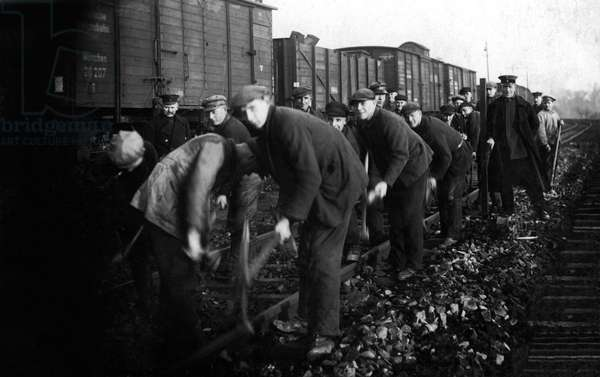 Railway workers (railway workers) working along the tracks near a freight train. Photography years 1924