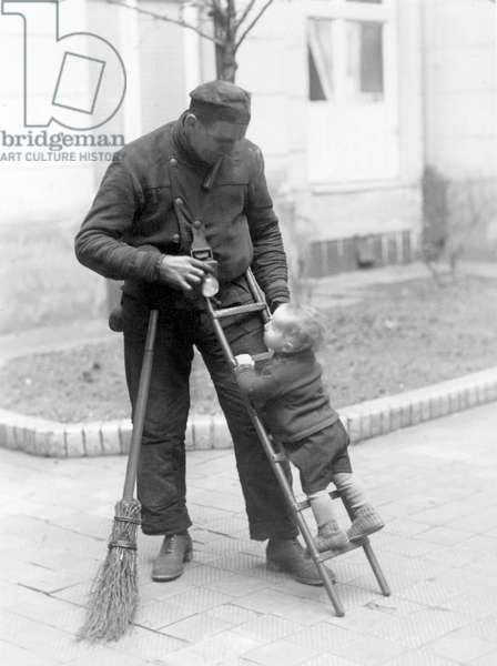A little boy in short panties climbs on a ladder supported by a chimney sweeper. 1920s.