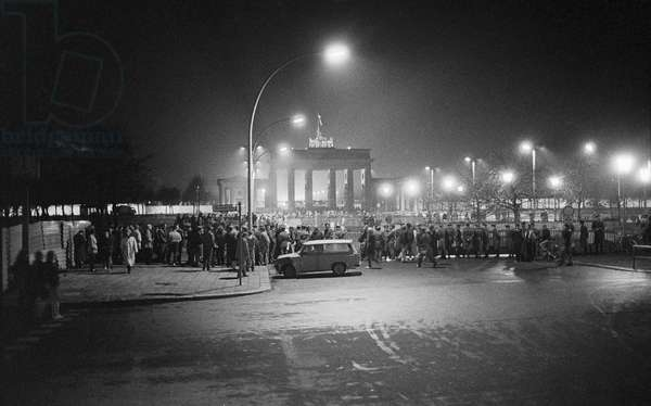 Fall of the Berlin Wall in November 1989: crowd gathered around the Brandenburg Gate on the night of 9 November 1989. Berlin, Germany. Fall of the Berlin Wall, on the night of the 9th November, 1989, a crowd gathered on the eastern side of the Brandenburg Gate, Berlin, Germany, Europe Photo Norbert Michalke