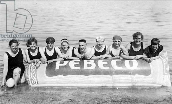 Group of swimmers in swimsuits with a pneumatics of the solar creme brand Pebeco on the beach by the sea. Photography around 1925