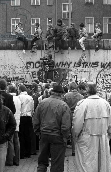 German reunification, Fall of the Berlin Wall, Germany, 1989: journalist near the wall waiting for East Berlin residents passing to the West. Photography