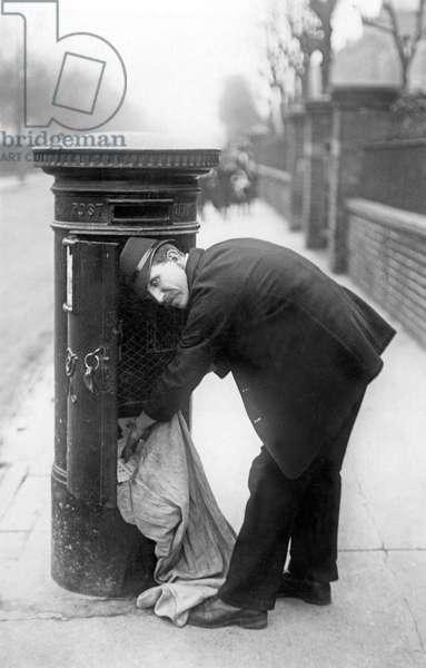 Postman picking up mail. Photography around 1920