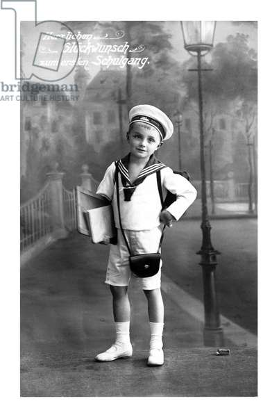 """Boy in sailor's uniform returning from school on the day of the rent with a slate and a notebook """"Herzlichen Glueckwunsch zum ersten Schulgang"""""""" (Felicitation for the first day of school)"""