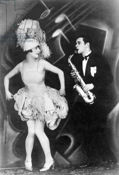 Woman dancing to the music of a jazz saxophonist. Photography around 1925
