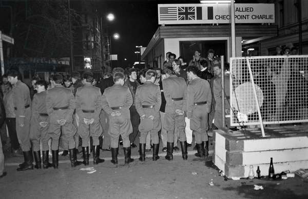 Fall of the Berlin Wall in November 1989: West German security forces (FRG or GDR) alline at Checkpoint Charlie checkpoint on the night of 9 November 1989. Berlin, Germany. Fall of the Berlin Wall, on the night of the 9th November, 1989, the border guards of the GDR have advanced up to the boundary line at Checkpoint Charlie, Berlin, Germany, Europe Photo Norbert Michalke