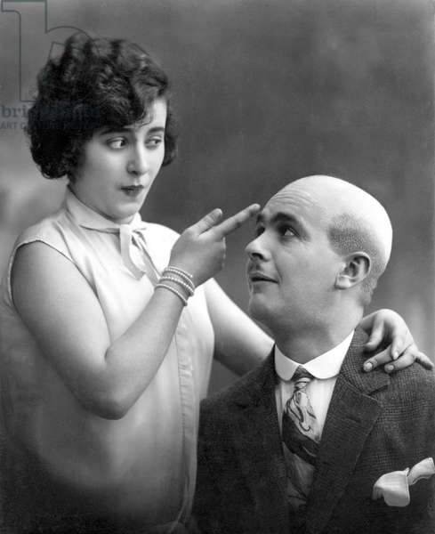 "Woman showing with one finger the skull of a bald man: ""Why does Egon have no hair? """" . Photography around 1920"