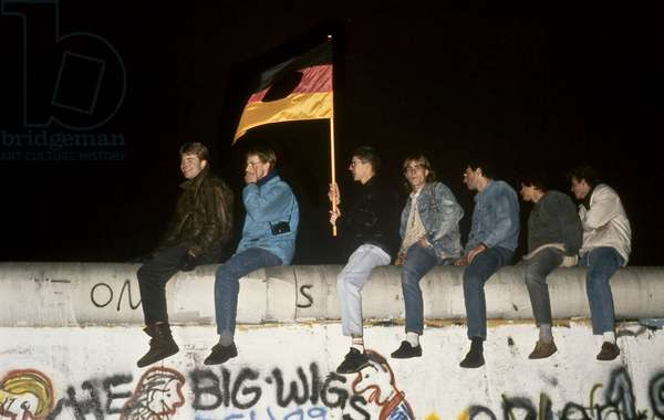 Fall of the Berlin Wall on the night of 9 November 1989: Berlin climbers on the Wall wield the German flag with the symbol of the GDR (DDR) in the vicinity of the Brandenburg Gate. Berlin. Fall of the Berlin Wall, on the night of the 9th November, 1989, people holding a flag with the insignia of the GDR cut out have climbed on the Wall at the Brandenburg Gate, Berlin, Germany, Europe Photo Norbert Michalke