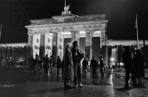 Fall of the Berlin Wall in November 1989: the Berlin people in the streets near the Brandenburg Gate on the night of 9 November 1989. Berlin, Germany. Fall of the Berlin Wall, on the night of the 9th November, 1989, citizens of Berlin standing speechless in the border area of the Brandenburg Gate, Berlin, Germany, Europe Photo Norbert Michalke