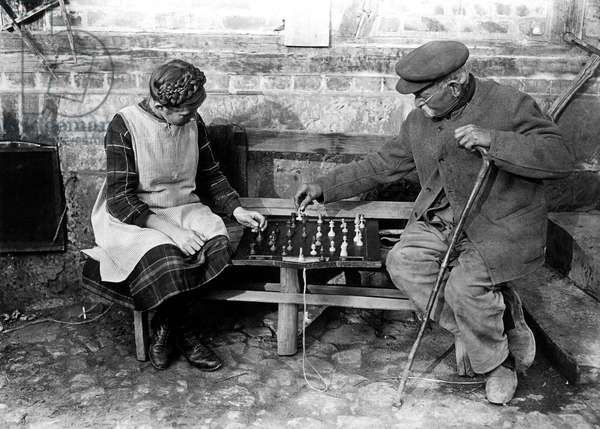 Grandfather (Grandfather) playing chess games with his little daughter on a bench. Photography around 1925