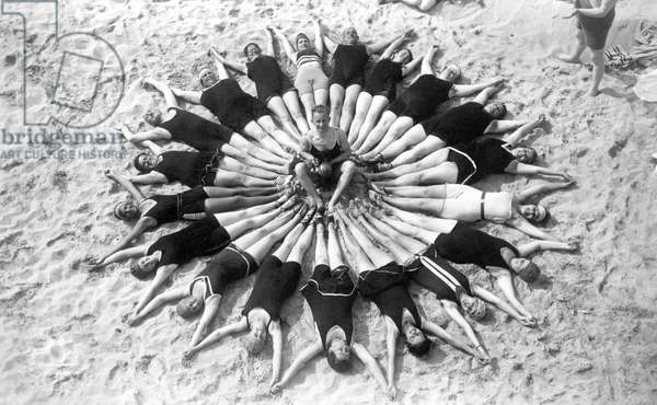 Group of swimmers in swimsuit forming a circle on the sand at the beach. Photography around 1920