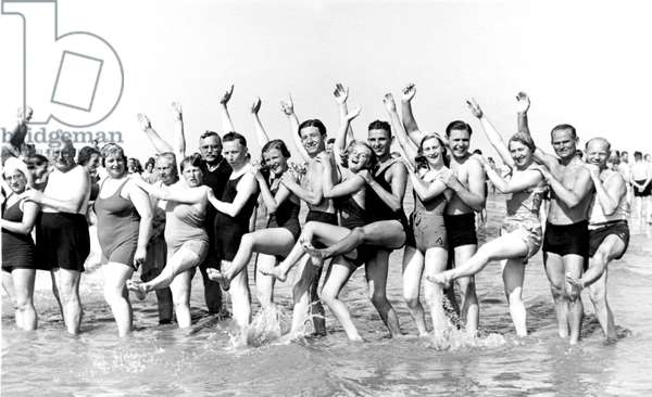 First paid holidays, seaside holidays: photograph of a group of holidaymakers in bathing suits at the beach, Germany 1920 approx. Historical photo, group of people at the beach, ca. 1920