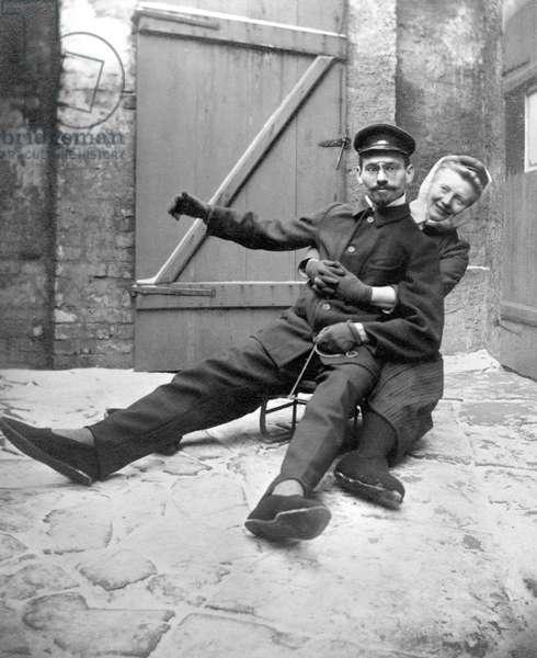 Couple having fun on a sledge in a courtyard.