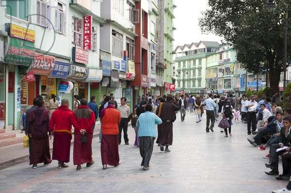 Buddhist monks strolling in the pedestrian zone; shopping street; Mahatma Gandhi Road; Gangtok; Sikkim; Himalayas; India; South Asia; Asia