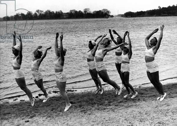 Sport: groups of women doing gymnastics at the water's edge. photography around 1929