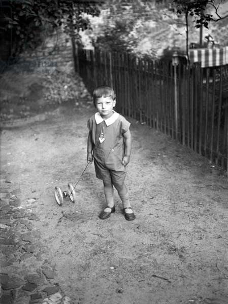 Little boy in short overalls, a toy in hand. Annees 1930 Germany Historic photograph, child with toy, thirties