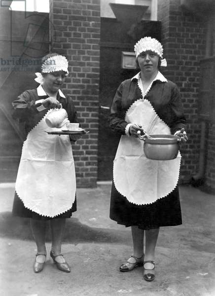 Two domestic women have the kitchen: one prepares the tea and the other makes a cake. Photography around 1920