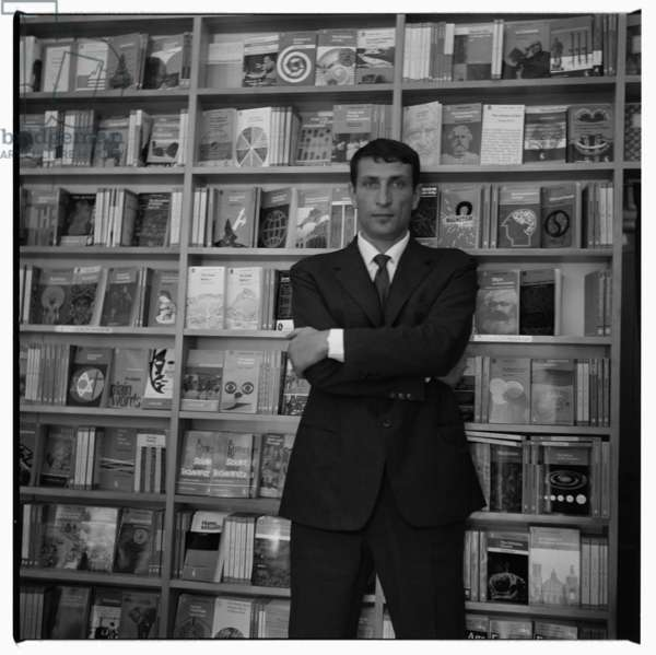 Germano Facetti, portrait of German Facetti influential graphic designer and head of cover design at Penguin Books, standing in front of Penguin book display, London early 1960's (b/w photo)