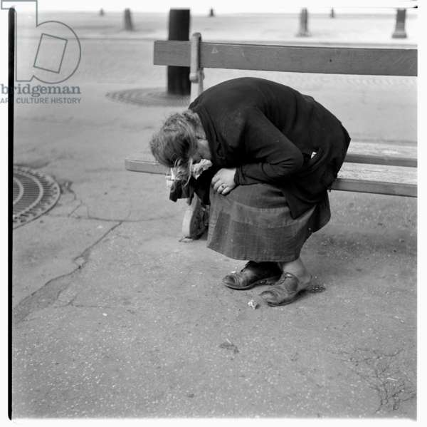 Image of a woman collapsing from drink or exhaustion, sat on a public bench, Paris early 1950's