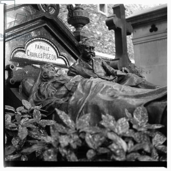 Image of the tombstone of Charles Pigeon, French inventor of a non-exploding gas lamp and also noted for his unique tombstone, Cimetiere de Montparnasse, Paris, early early 1950's
