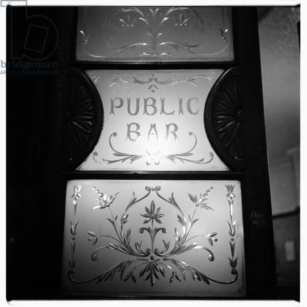 London, Public bar glass door, image from a night walk round central London, showing the etched glass saloon door of a pub, London 1957