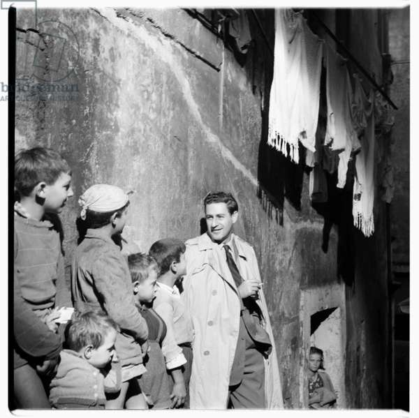 Cigarette advert, photograph of model posing for cigarette advert with street children, Rome, Italy, mid 1950's (b/w photo)