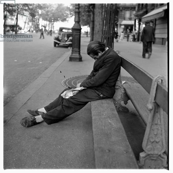 Image of a man asleep, possibly drunk on a bench, Paris, early early 1950's