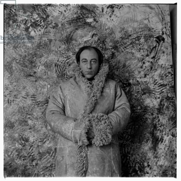 Portrait of the artist Tony Stubbing in his studio standing in front of his own painting, London early 1960's