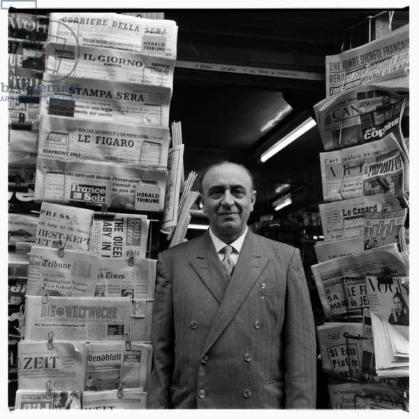 Enzo standing outside newsagency, c.1955 (b/w photo)