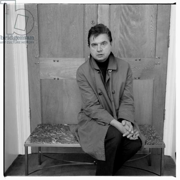 Portrait of the artist Francis Bacon wearing polo neck and mac, London, early 1960's