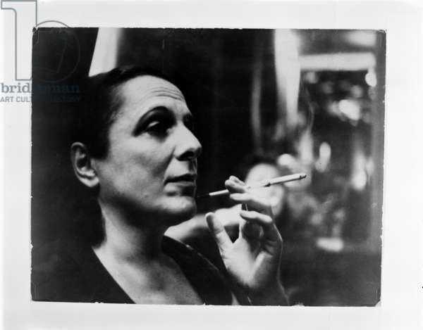 Muriel Belcher, portrait of Muriel Belcher, Colony Room proprietor and model for Francis Bacon, smoking with a cigarette holder, Soho, London mid 1950's