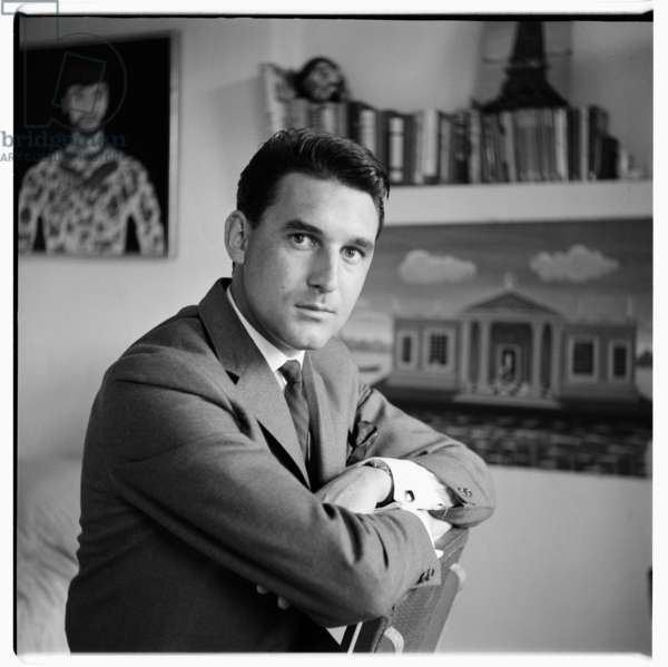 Unknown man with Deakin painting, portrait of unknown man with John Deakin paintings in background, London, UK, mid 1960's (b/w photo)