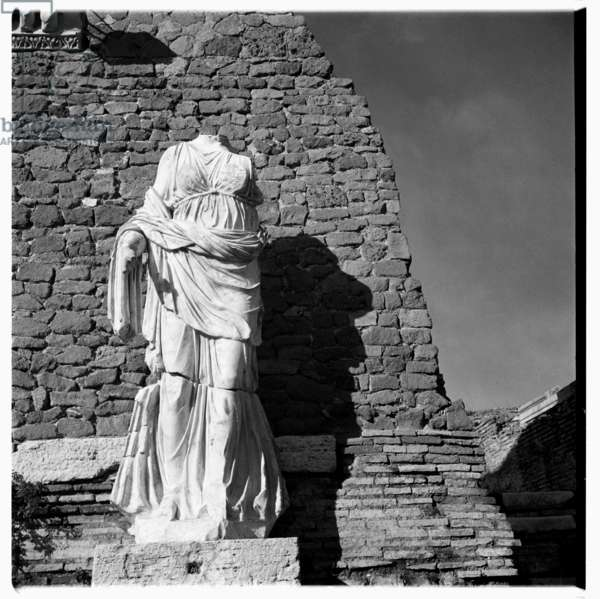Image of a headless classical statue, possibly Greek or Roman, wearing toga, head missing, possibly Rome or Paris, early early 1950's