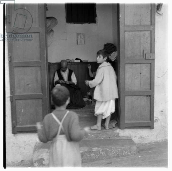 Children entering into house, Tangier, early 1960's (b/w photo)