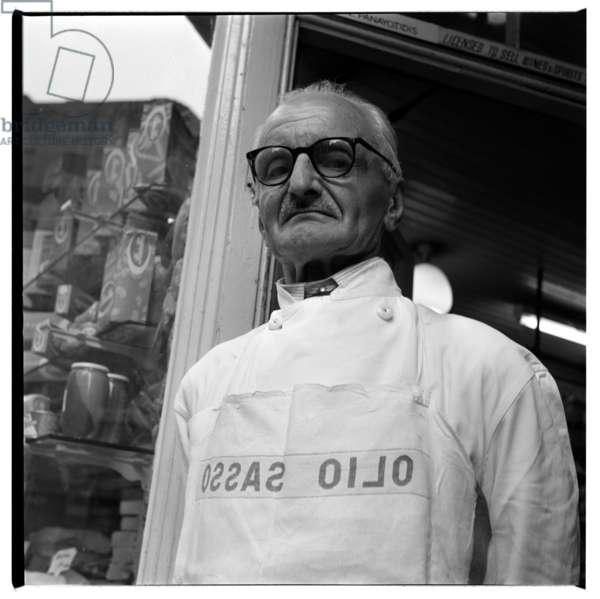 Bomba, standing outside Lina Stores, portrait of Bomba, Oil Merchant, standing outside Lina Stores Italian delicatessen, Brewer St Soho London, late 1950's (b/w photo)