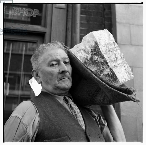 Jeeman - Ice carrier, portrait of a Soho character called Jeeman carrying chuck of ice in street, Soho, London mid 1950's (b/w photo)
