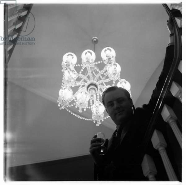 Tony Hubbard, portrait shot in stairwell with chandelier in above (b/w photo)